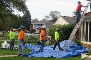 Waukegan Roofing crew members get ready to pass donated material to waiting personnel on the roof.